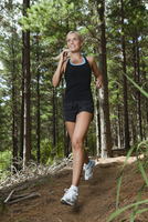 Woman running on dirt path in forest