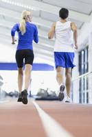 Couple running on indoor track in gym