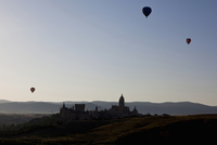 Hot air balloons floating over castle