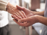 Nurse holding older mans hand