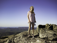 Hiker standing on top of rocky mountain