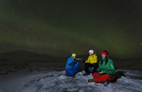 Hikers relaxing under aurora borealis