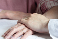 Doctor holding older womans hand