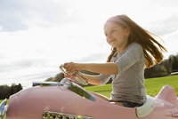 Girl driving toy airplane in field