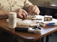 Older man measuring out medication