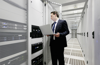 Businessman using laptop in server room