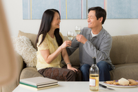Mature couple sitting on sofa toasting white wine