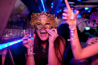 Young woman wearing mask with wine glass in limousine