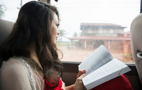 Woman looking out of window on bus with book
