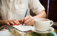 Woman writing postcard in cafe