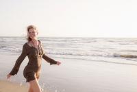 Mature woman walking along beach, smiling