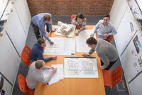 Team of architects discussing plans in meeting room