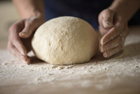 Close up of hands shaping bread dough