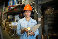 Portrait of young woman in warehouse with clipboard