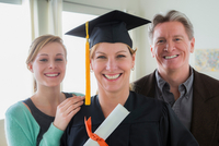 Mother wearing mortarboard with daughter and husband