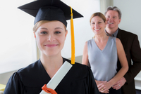 Teenage girl wearing mortarboard with parents in background