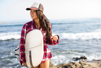 Young woman wearing baseball cap with surfboard