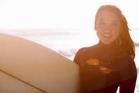 Young woman wearing wetsuit with surfboard