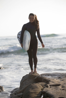 Young woman standing on rocks with surfboard