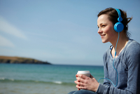 Young woman at coast with coffee and earphones