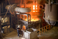 Elevated view of steel worker and furnace in steel foundry
