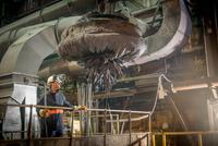 Steel worker overseeing industrial magnet at work in steel f