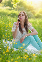 Young woman sitting in meadow blowing dandelion clock