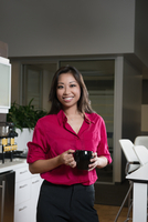 Young businesswoman holding mug in office kitchen, portrait