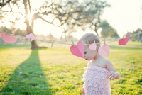 Young girl next to heart shapes on washing line 11015233657| 写真素材・ストックフォト・画像・イラスト素材|アマナイメージズ