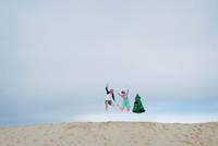 Young couple leaping on beach