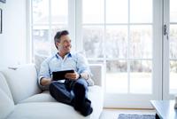 Man relaxing on sofa using digital tablet