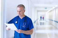 Doctor standing in corridor reading medical records
