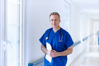 Doctor standing in corridor holding medical records