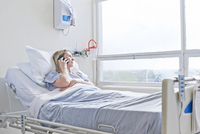 Patient lying on hospital bed on telephone call
