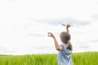 Girl in field with toy aeroplane