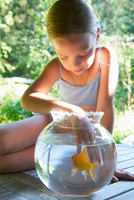 Young girl with fingers in goldfish bowl