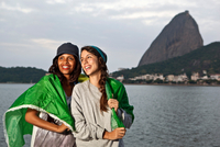 Two female friends wrapped in flag, Rio de Janeiro, Brazil