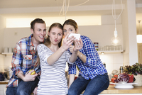 Three young people having fun taking photographs in the kitchen