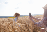 Mother photographing girl running through wheat field
