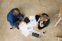 Young business partners sitting on floor in design office