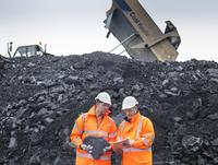 Coal miners inspecting coal in surface coal mine