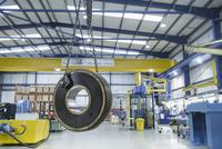 Heavy engineering gear hanging from crane in factory 11015239694| 写真素材・ストックフォト・画像・イラスト素材|アマナイメージズ