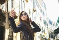 Girl taking selfie on smartphone, Venice, Italy