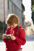 Young boy checking photographs on street, Province of Venice, Italy