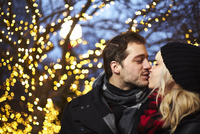 Young couple kissing in front of outdoor xmas lights