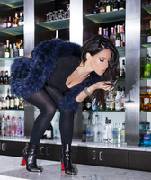 Mid adult woman in cocktail bar bending forward holding drink