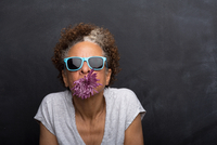 Studio portrait of senior woman with flower in her mouth 11015240141| 写真素材・ストックフォト・画像・イラスト素材|アマナイメージズ