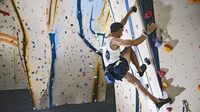 Mature man climbing with ropes on climbing wall