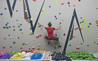 Route setter trying bouldering problem at indoor climbing wall