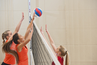 Volleyball players hitting ball over net